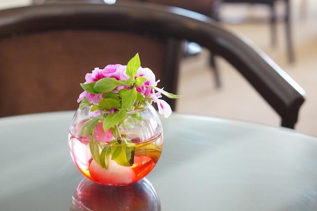 Mooie decoratie van roze bloemen in een glazen vaas op tafel in een kamer