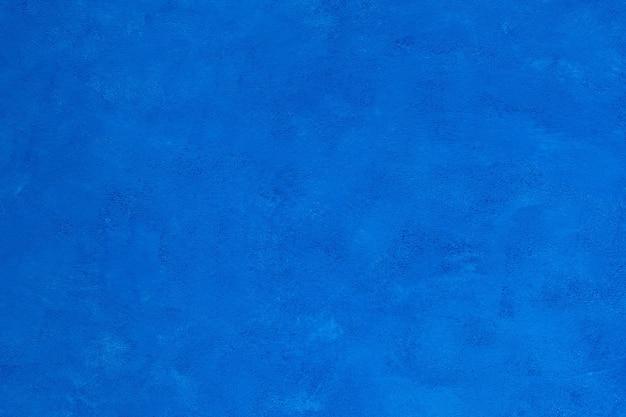 Mooie decoratieve helderblauwe achtergrond met mooie ruwe textuur voor ontwerp en decoratie.
