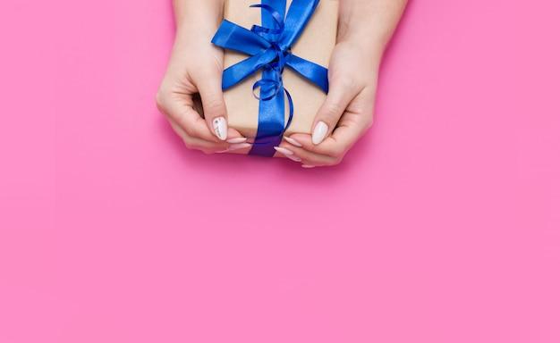 Mooie delicate vrouwelijke manicure houdt het geschenk in een eco-wrap met blauw satijnen lint op een roze oppervlak