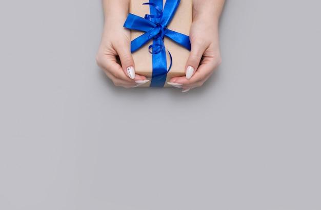 Mooie delicate vrouwelijke manicure houdt het geschenk in een eco-wrap met blauw satijnen lint.