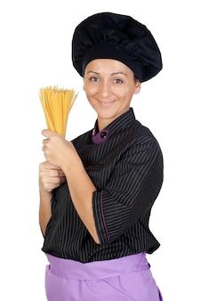 Mooie die kokvrouw met spaguettis op witte achtergrond wordt geïsoleerd