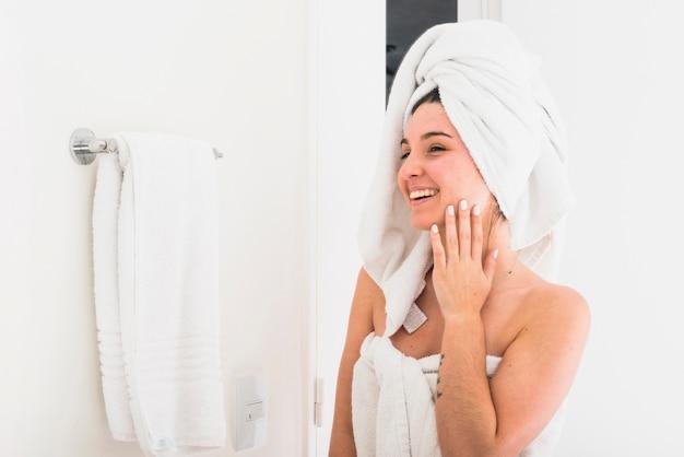 Mooie die vrouw met handdoek op hoofd wordt verpakt die in de spiegel kijken
