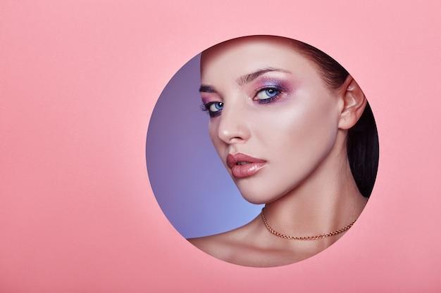 Mooie dikke lippen felroze kleur, vrouw kijkt in cirkelgat gekleurd roze papier, schoonheidssalon.