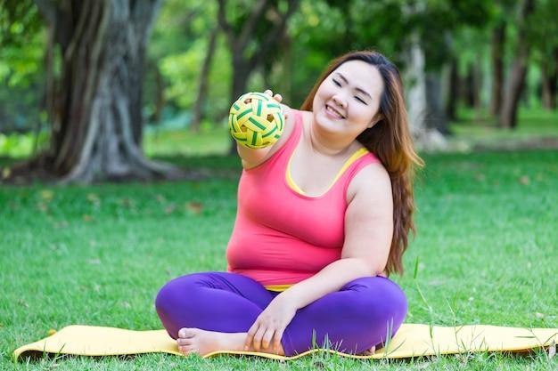 Mooie dikke vrouw spelen met plastic bal op de mat