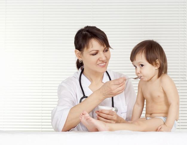 Mooie dokter met klein meisje in haar kantoor