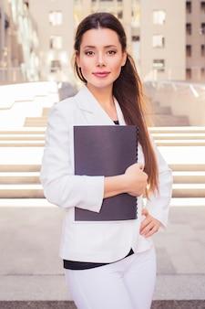 Mooie donkerbruine bedrijfsvrouw in wit kostuum met omslag van documenten in haar handen in openlucht