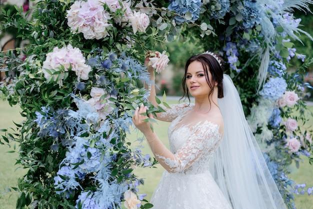 Mooie donkerbruine bruid dichtbij de overwelfde galerij die van blauwe hortensia en ruscus wordt gemaakt, huwelijksdag