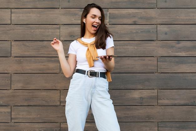 Mooie donkerbruine jonge gelukkige vrouw die vrijetijdskleding draagt en aan muziek luistert via draadloze oortelefoons