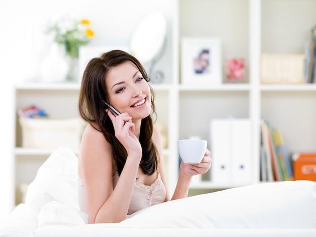 Mooie donkerbruine jonge vrouw die door mobiele telefoon spreekt en een kopje koffie drinkt