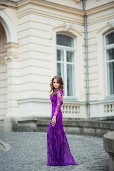 Mooie donkerbruine jonge vrouw die kleding draagt en op de straat loopt