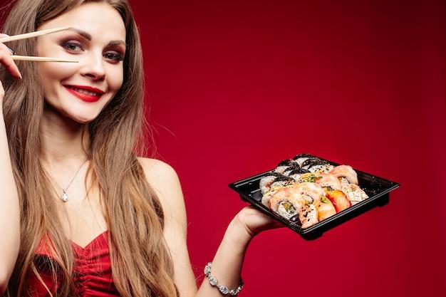 Mooie donkerbruine jonge vrouw met doos sushi en stokken op rood.