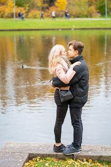 Mooie donkerbruine kerel en mooie meisjesblonde op datum. liefdevolle tieners zijn blij, glimlachen, kussen.