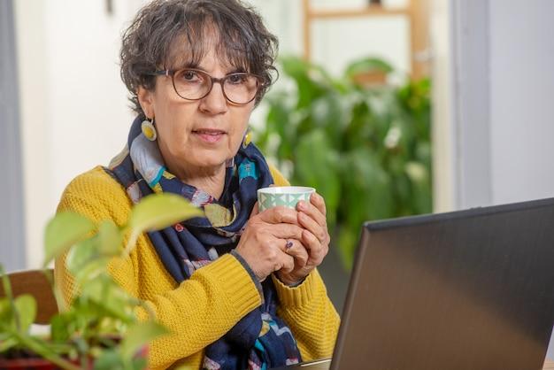 Mooie donkerbruine rijpe vrouw die in gele het drinken kop thee draagt
