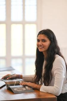 Mooie donkerbruine student terwijl het lesgeven van haar les en het zitten bij het houten bureau over comfortabele woonkamer
