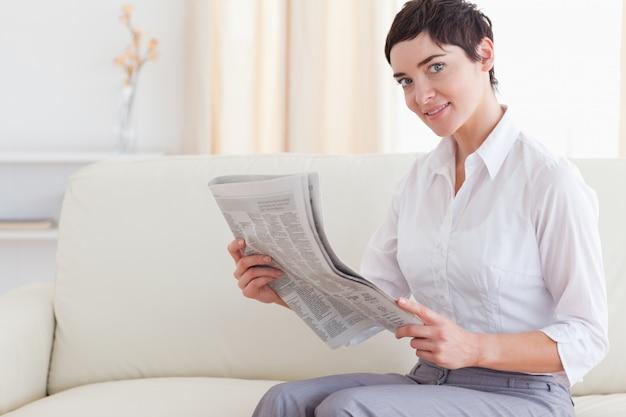 Mooie donkerbruine vrouw die het nieuws leest