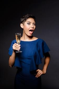 Mooie donkerbruine vrouw die in avondjurk knipogen, champagneglas houden