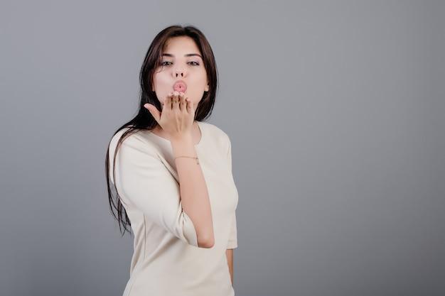 Mooie donkerbruine vrouw die knuffel kus met hand verzendt die over grijs wordt geïsoleerd