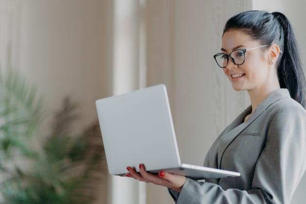 Mooie donkerbruine vrouw die laptop met behulp van