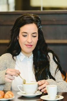 Mooie donkerbruine vrouw die ontbijt het drinken koffie in een europees restaurant heeft.
