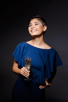 Mooie donkerbruine vrouw in avondjurk glimlachen, die champagneglas houdt