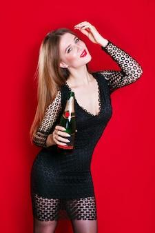 Mooie donkerbruine vrouw in en avondjurk die glimlacht kijkt, die champagne houdt
