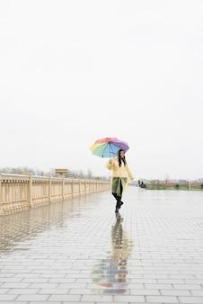 Mooie donkerbruine vrouw in gele regenjas die regenboogparaplu in de regen houdt
