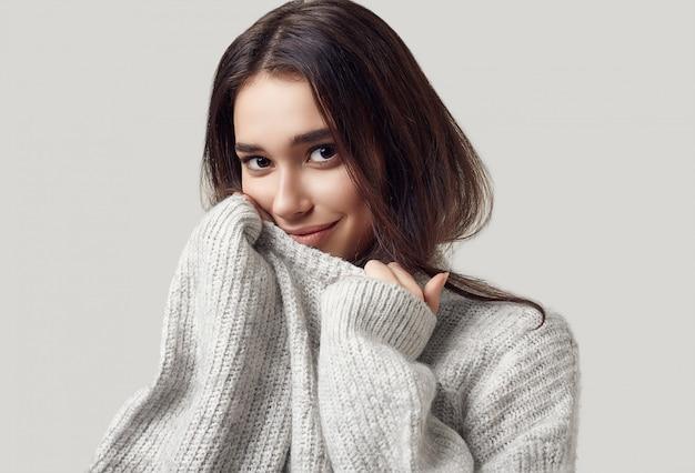 Mooie donkerbruine vrouw in sweater het stellen in studio