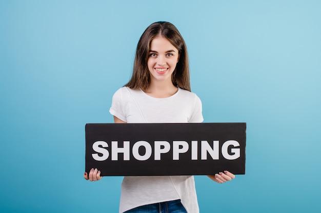 Mooie donkerbruine vrouw met copyspacetekst het winkelen tekenbanner die over blauw wordt geïsoleerd