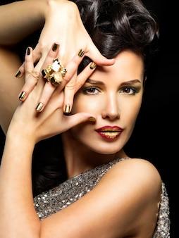 Mooie donkerbruine vrouw met gouden spijkers en stijlmake-up van ogen - op zwarte achtergrond