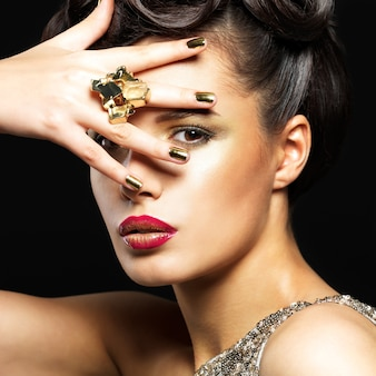 Mooie donkerbruine vrouw met gouden spijkers en stijlmake-up van ogen