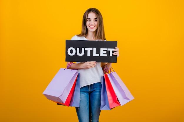Mooie donkerbruine vrouw met kleurrijke die het winkelen zakken en copyspace de afzetteken van de tekst over geel wordt geïsoleerd