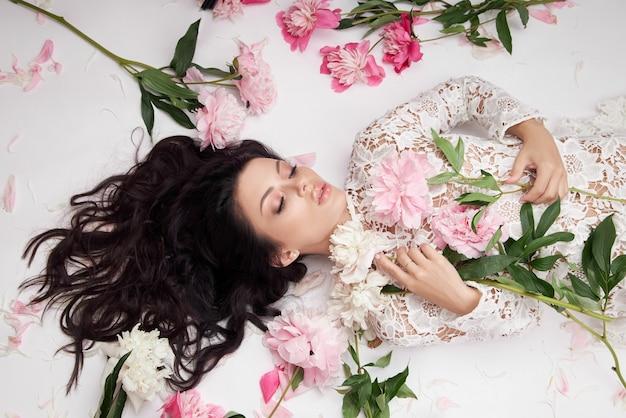 Mooie donkerbruine vrouw met pioenbloemen. natuurlijke cosmetica en make-up, perfecte huid