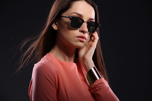 Mooie donkerbruine vrouw met zonnebril en het lange haar stellen