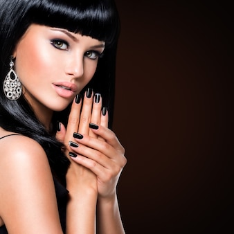 Mooie donkerbruine vrouw met zwarte spijkers en maniermake-up van ogen. meisje met recht kapsel in de studio