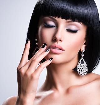 Mooie donkerbruine vrouw met zwarte spijkers en maniermake-up van ogen