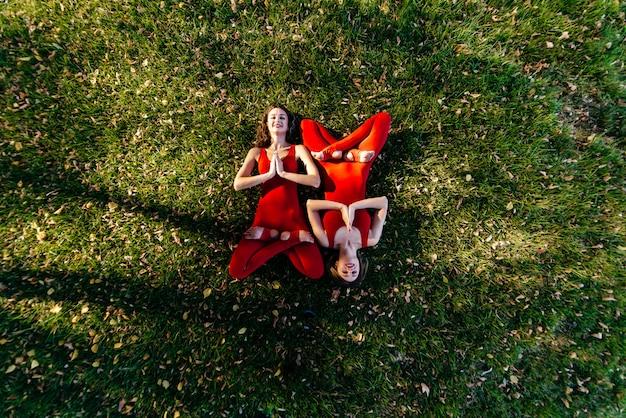Mooie donkerbruine vrouw twee die strakke actieve slijtage dragen die yoga uitvoeren stelt in een park op purpere matten met zachte zongloed die door de bomen komen