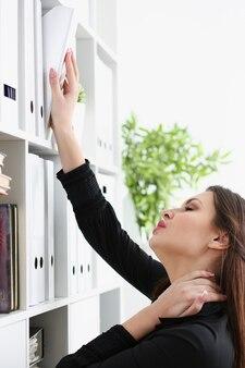 Mooie donkerbruine vrouwelijke bediende die naar juist document zoekt