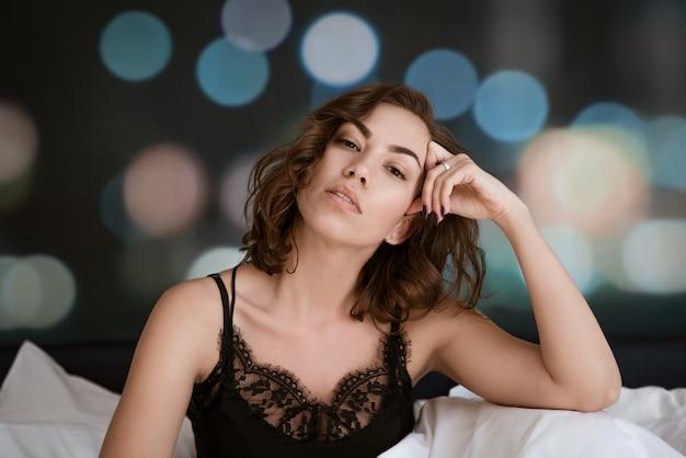 Mooie donkerbruine vrouwenzitting in bed, ochtendontspanning