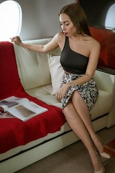 Mooie donkerbruine vrouwenzitting in een privé vliegtuigzetel