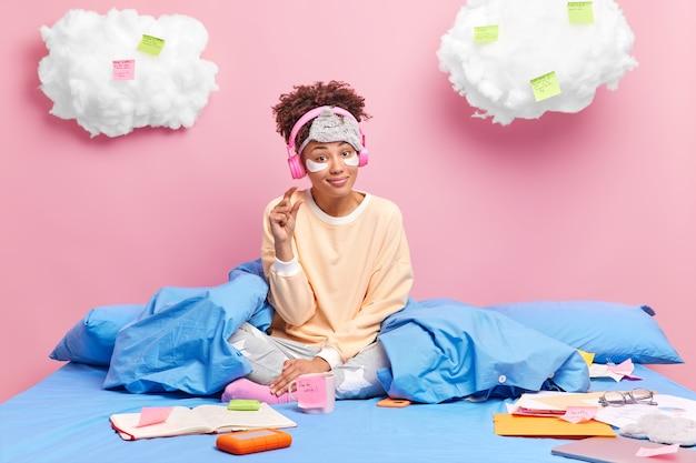 Mooie donkere gevilde krullende vrouw in comfortabel pyjama gebaar klein gebaar