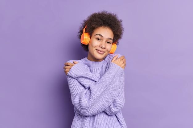 Mooie donkere huid duizendjarige meisje omhelst zichzelf raakt schouders geniet van zachtheid van haar nieuwe trui luistert aangename melodie via stereohoofdtelefoon
