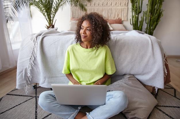 Mooie donkere huid jonge vrouw met krullend bruin haar poseren over interieur, sittinig voor bed in de slaapkamer, bedachtzaam opzij kijken met zachte glimlach