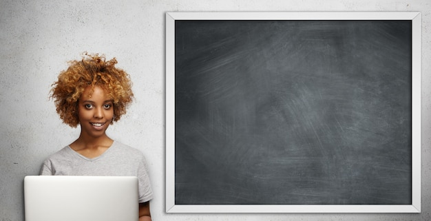 Mooie donkere jonge vrouwelijke leraar met stijlvolle kapsel controleren papieren van haar studenten, met behulp van laptop in de klas