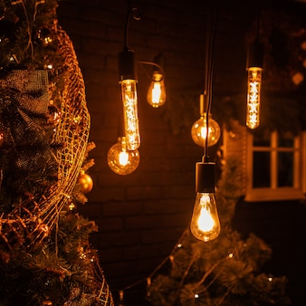 Mooie donkere kamer met oude lampen met geel licht en een kerstboom met gouden speelgoed en vintage slingers