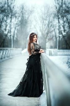 Mooie donkere koningin. girl gothic princess met een kroon in een lange donkere jurk.