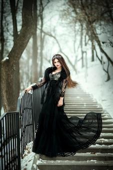 Mooie donkere koningin. gotische prinses met een kroon in een lange donkere jurk.