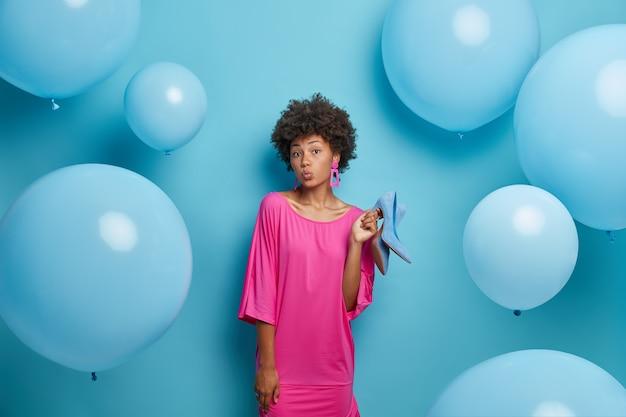 Mooie donkere krullende afro-amerikaanse vrouw houdt lippen rond, gekleed stijlvolle jurk, houdt schoenen vast, kiest wat te dragen of kleden, geïsoleerd op blauwe muur met opgeblazen ballonnen rond.