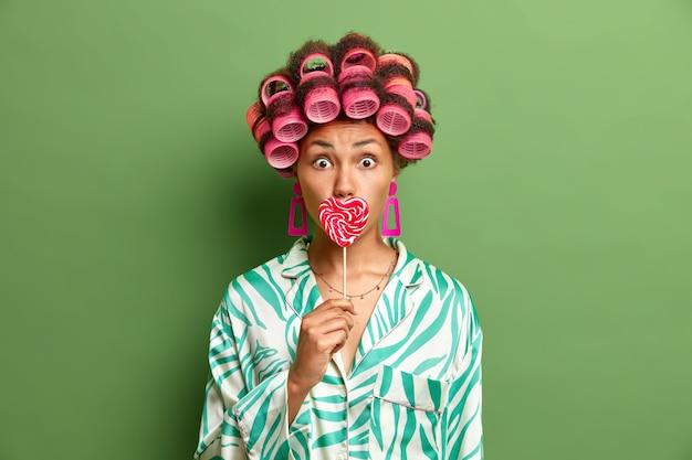 Mooie donkere vrouw bedekt mond met zoete snoepjes, haarrollers dragen oorbellen en zijden kamerjas geïsoleerd over felgroene muur. huisvrouw houdt lollystandaards binnen