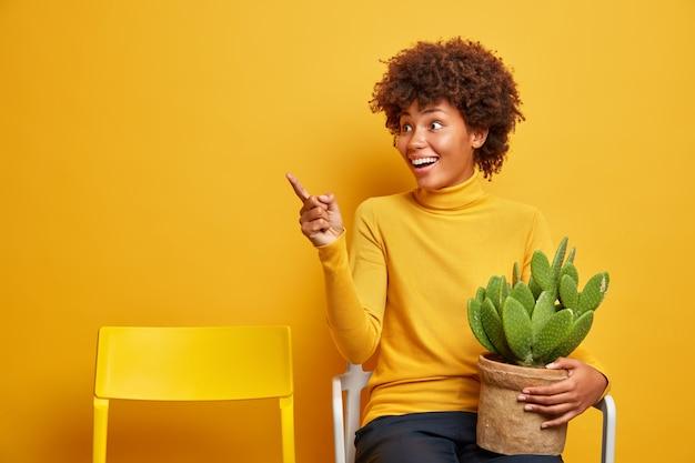 Mooie donkere vrouw bloemist zorgt voor huisplanten draagt pot met cactus houdingen op stoel en wijst in de verte met vrolijke uitdrukking