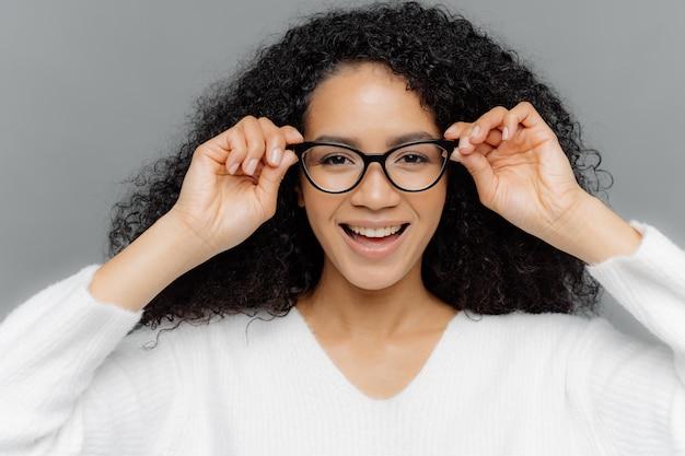 Mooie donkere vrouw heeft minimale make-up, houdt handen op frame van transparante bril